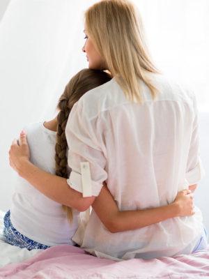 Mutter hält ihre Tochter im Arm - Thema Mädchensprechstunde